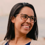 Portrait of Rosario Villarreal, she has straight black hair, tortoise shell glasses, and a wide smile.